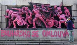 A cameraman films the figures of Soviet soldiers at the base of the Soviet Army monument in Sofia, painted in pink by an unknown artist August 21, 2013. REUTERS/Stoyan Nenov