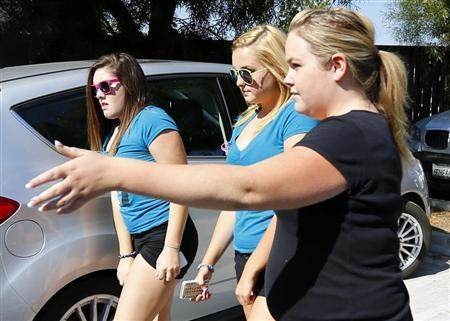Rescued kidnapping victim Hannah Anderson (C), 16, is escorted into a local restaurant that was holding a raffle and donating profits to help cover the Anderson family funeral costs in Lakeside, California, August 15, 2013. REUTERS/Mike Blake