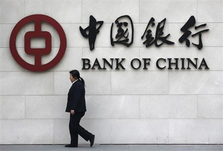 A woman walks past a sign of Bank of China at its branch in Beijing March 26, 2013. REUTERS/Kim Kyung-Hoon
