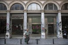 A man carries shopping bags on a street with closed shops in Athens August 12, 2013. REUTERS/Yorgos Karahalis