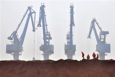 Workers remove the cloth covering the iron ore from Australia while they prepare for transporting at a port in Tianjin municipality in this March 29, 2010 file photo. REUTERS/Vincent Du/Files