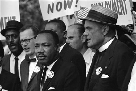 8月22日、米公民権運動の指導者マーティン・ルーサー・キング牧師が人種差別の撤廃を訴えた演説から半世紀を経ったが、米国民の約半数は肌の色による差別撤廃が「まだ道半ば」と感じていることが調査で分かった。写真は1963年8月にワシントンでのデモに参加したキング牧師(中央)(2013年 ロイター/Rowland Scherman/U.S. Information Agency/U.S. National Archives)