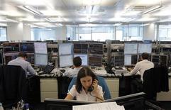 Трейдеры в торговом зале инвестбанка Ренессанс Капитал в Москве 9 августа 2011 года. Российские фондовые индексы слабо изменились в начале торгов пятницы после опережающего остальные развивающиеся рынки роста накануне. REUTERS/Denis Sinyakov