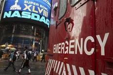 Автомобиль экстренных служб проезжает у биржи Nasdaq в Нью-Йорке 22 августа 2013 года. Биржа Nasdaq, где обращаются бумаги на сумму $5,9 триллиона, на три часа прекратила работу в четверг вечером, погрузившись во тьму из-за отключения электричества, сообщили представители торговой площадки. REUTERS/Lucas Jackson