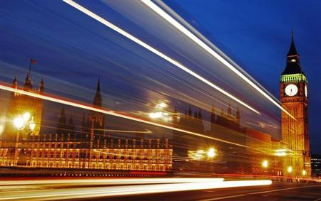 Light trails made by a passing bus illuminate the night sky in front of Britain's Houses of Parliament in London, February 4, 2010. REUTERS/Luke Macgregor