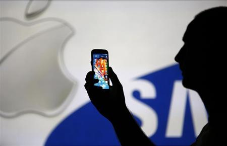 A man is silhouetted against a video screen with Apple and Samsung logos as he poses with a Samsung S4 smartphone in this photo illustration taken in the central Bosnian town of Zenica, August 14, 2013. REUTERS/Dado Ruvic
