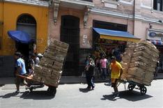 Unos trabajadores trasladan unos carretones a lo largo del mercado central de Lima, abr 8 2013. La economía peruana aceleró su ritmo de crecimiento en el segundo trimestre debido a que un repunte del gasto público e inversiones y una sólida demanda interna compensaron una caída de las exportaciones, dijo el viernes el Gobierno. REUTERS/Mariana Bazo
