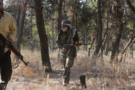 A member of the 'Liwaa Ahrar Suriya' brigade, operating under the Free Syrian Army, is seen in a public park that separates them and forces loyal to President Bashar al-Assad in Sakhour area, Aleppo August 24, 2013. REUTERS/Muzaffar Salman