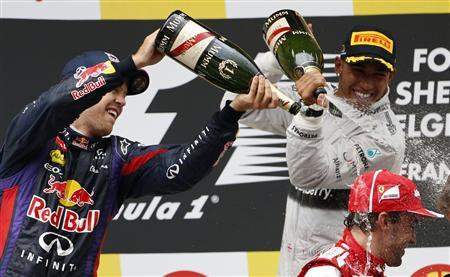 Winner Red Bull Formula One driver Sebastian Vettel of Germany (L) and third-placed Mercedes Formula One driver Lewis Hamilton of Britain (back R) pour champagne on second-placed Ferrari Formula One driver Fernando Alonso of Spain during the Belgian F1 Grand Prix at the Circuit of Spa-Francorchamps August 25, 2013. REUTERS/Francois Lenoir