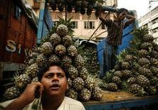 Продавец ананасов говорит по телефону на рынке в Калькутте 2 апреля 2008 года. Индийское мобильное отделение российской группы Система сократило убыток во втором квартале 2013 года за счет сворачивания ряда операций после судебного решения. REUTERS/Jayanta Shaw
