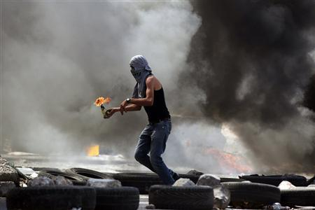 A Palestinian protester gets ready to throw a Molotov cocktail during small clashes with Israeli forces following the funerals of Robin Zayed, Younis Jahjouh and Jihad Aslan at Qalandiya Refugee Camp near the West Bank city of Ramallah August 26, 2013. REUTERS/Darren Whiteside