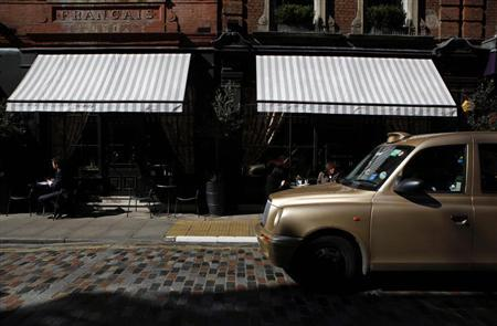 A taxi passes patrons sitting at a hotel restaurant's street tables in Covent Garden, central London March 27, 2012. REUTERS/Andrew Winning