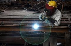 A worker welds at a machinery manufacturing factory in Huaibei, Anhui province August 20, 2013. China's factory activity in August may have expanded at the fastest pace in three months, a Reuters poll showed, adding to evidence that the world's second-largest economy may be stabilising after slowing for more than two years. REUTERS/Stringer