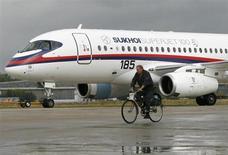 Велосипедист проезжает мимо самолета Sukhoi Superjet 100, участвующего в авиасалоне МАКС-2009 в Жуковском, 14 августа 2009 года. Российские компании договорились во вторник в ходе авиасалона МАКС о продаже десятков самолетов и вертолетов, при этом основное внимание было приковано к лайнерам Superjet и МС-21. REUTERS/Sergei Karpukhin