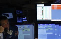 Trader au New York Stock Exchange. Les autorités américaines ont demandé à Nasdaq OMX Group et à NYSE Euronext de leur exposer l'enchaînement des événements de la journée de jeudi dernier, marquée par l'interruption pendant plus de trois heures de toutes les cotations sur le Nasdaq, mais les deux opérateurs rivaux ont des versions différentes, selon plusieurs sources proches du dossier. /Photo prise le 27 août 2013/REUTERS/Brendan McDermid