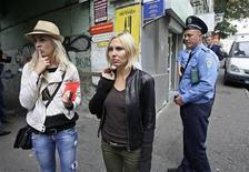 Активистки Femen Яна Жданова (в центре) и Александра Шевченко стоят у офиса группы в Киеве 27 августа 2013 года. Украинская феминистская группа Femen, получившая известность благодаря своим акциям топлесс, заявила, что украинская милиция во время обыска в офисе организации во вторник подбросила взрывчатые вещества и пистолет. REUTERS/Gleb Garanich