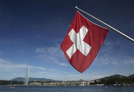A Swiss flag is pictured next to the Jet d'Eau (water fountain), and the Lake Leman from the St-Pierre Cathedrale in Geneva June 5, 2012. REUTERS/Denis Balibouse