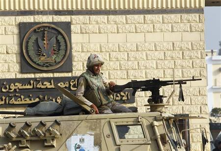 An Egyptian army soldier guards on an armoured personnel carrier in front of the main gate of Torah prison where deposed leader Hosni Mubarak is detained in, on the outskirts of Cairo, August 22, 2013. REUTERS/Louafi Larbi