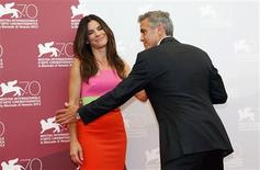 U.S. actor George Clooney (R) poses with actress Sandra Bullock during a photocall at the 70th Venice Film Festival in Venice August 28, 2013. REUTERS/Alessandro Bianchi