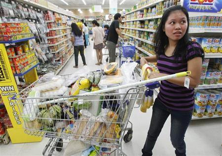 A customer pushes a trolley as she shops at a grocery store in Manila's Makati financial district November 29, 2012. REUTERS/Romeo Ranoco