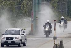 A U.S. Army vehicle escorts two New Zealanders driving their motorbikes as they arrive at the CIQ (Customs, Immigration and Quarantine) office, just south of the demilitarized zone (DMZ) separating the two Koreas, in Paju, north of Seoul August 29, 2013. Five motorcyclists from New Zealand travelled through North Korea, beginning on August 16, 2013, and reached the South on Thursday by crossing over the DMZ, local media reported. The five New Zealanders wanted to use their visit to wish for peace on the Korean Peninsula. REUTERS/Lee Jae-Won