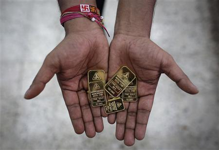 An employee poses with gold biscuits inside a jewellery showroom in Mumbai June 4, 2013. REUTERS/Danish Siddiqui