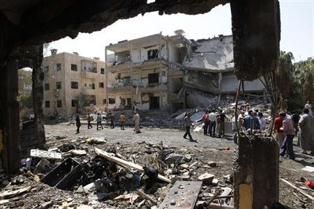 People inspect the damage at a site hit by what activists say was a car bomb in Raqqa province, eastern Syria August 29, 2013. REUTERS/Nour Fourat