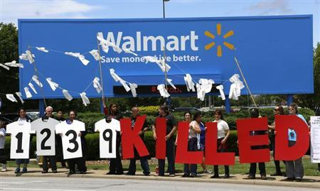 Protesters hold up a sign commemorating those killed in recent clothing factory tragedies in Bangladesh outside Wal-Mart Stores Inc. headquarters in Bentonville, Arkansas June 5, 2013. REUTERS/Rick Wilking
