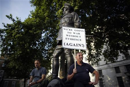 A protestor holds a placard during a rally against the proposed attack on Syria in central London August 28, 2013. REUTERS-Olivia Harris