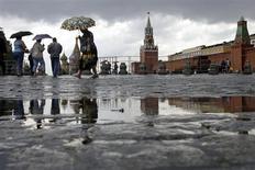 Люди идут под зонтами по Красной площади в Москве, 30 июня 2008 года. Наступающие выходные в Москве будут прохладными и пасмурными, ожидают синоптики. REUTERS/Denis Sinyakov