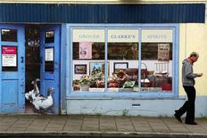 A man walks past an empty shop, which has been covered with artwork to make it look more appealing, in the village of Bushmills on the Causeway Coast August 19, 2013. REUTERS/Cathal McNaughton