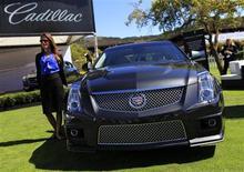 Женщина стоит около автомобиля Cadillac CTS-V на автошоу в Калифорнии, 16 августа 2013 года. Cadillac, бренд автомобильного гиганта General Motors Co, планирует расширить к 2017 году модельный ряд дорогих кроссоверов и отвоевать часть рынка у аналогичных машин немецких конкурентов. REUTERS/Michael Fiala