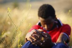 A migrant, who said he was from Somalia, sits on the ground after being apprehended by the Serbian border police, having illegally entered the country from Macedonia, near the town of Presevo some 383 km (238 miles) from capital Belgrade July 17, 2013. Every year, the Serbian border police catch thousands of migrants from Africa, the Middle East, and elsewhere who are trying to reach Serbia illegally. In many cases they come from Turkey, through Greece to Macedonia and Serbia before they reach Hungary and with it, the borderless Schengen travel zone. With chaos and conflict raging in Syria, last year saw a huge increase in the number of Syrians trying to enter the Western Balkans in search of asylum in the West. Picture taken July 17, 2013. REUTERS/Marko Djurica