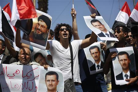 Palestinian protesters hold pictures of Syria's President Bashar al-Assad and Hezbollah leader Sayyed Hassan Nasrallah during a demonstration against potential strikes on the Syrian government, in the West Bank City of Ramallah August 31, 2013. REUTERS/Mohamad Torokman