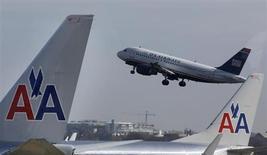 American Airlines et US Airways seront fixés en décembre au plus tard sur leur projet de méga-fusion qui doit donner naissance à la première compagnie aérienne mondiale, le procès opposant les deux compagnies au département de la Justice et à plusieurs Etats opposés à leur rapprochement devant débuter le 25 novembre. /Photo prise le 25 février 2013/REUTERS/Larry Downing
