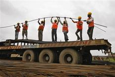 Workers unload iron rods from a truck at the construction site of an educational institute on the outskirts of western Indian city of Ahmedabad August 30, 2013. REUTERS/Amit Dave