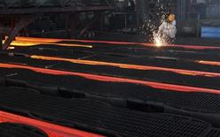 A worker cuts crude steel on a production line at a steel factory in Ganyu, Jiangsu province July 11, 2013. REUTERS/China Daily