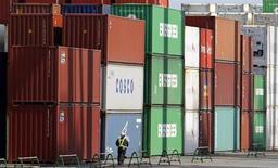 Человек на велосипеде проезжает мимо контейнеров в порту в Токио 19 августа 2013 года. Один из крупнейших в РФ портовых операторов Global Ports покупает 100 процентов Национальной контейнерной компании (НКК), говорится в сообщении Global Ports на Лондонской фондовой бирже. REUTERS/Toru Hanai