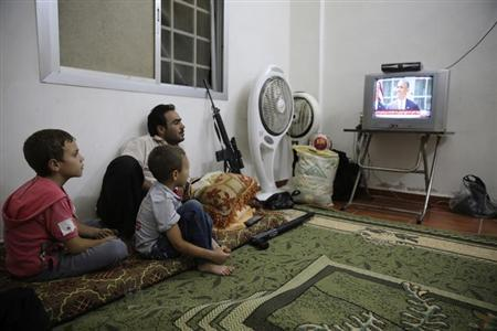 A Free Syrian Army fighter watches U.S. President Barack Obama's speech with his family in Ghouta, Damascus August 31, 2013. REUTERS/ Mohamed Abdullah