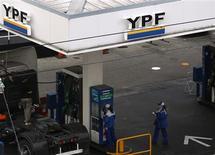 La petrolera estatal argentina YPF elevó su producción de hidrocarburos en un 4,7 por ciento interanual en julio, al acumular un alza del 1,1 por ciento en los primeros siete meses del 2013, dijo la firma en un comunicado difundido el lunes. En la foto de archivo, empleados de YPF en una estación de gasolina en Buenos Aires. Mayo 23, 2013. REUTERS/Marcos Brindicci