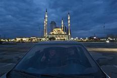 """Мужчины позируют фотографу в машине на фоне мечети """"Сердце Чечни"""" в Грозном 22 апреля 2013 года. Чеченский офис крупного российского оператора связи засыпан осколками, стекла разбиты, стены вымазаны засохшим яичным желтком. REUTERS/Maxim Shemetov"""