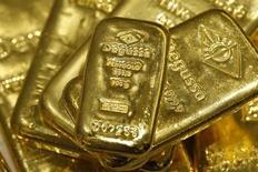 Золотые слитки в хранилище отделения трейдера Degussa в Цюрихе 19 апреля 2013 года. Цены на золото незначительно понизились в связи с задержкой военного удара США по Сирии и улучшением мировой экономической статистики, которые снизили привлекательность золота как низкорискованного вложения. REUTERS/Arnd Wiegmann