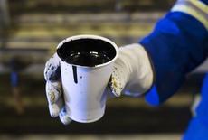 """Рабочий держит стакан """"тяжелой"""" нефти, добытой на проекте SAGD компании Cenovus Energy на озере Кристина в канадской провинции Альберта, 15 августа 2013 года. Цены на нефть Brent растут после ракетных испытаний Израиля в Средиземном море, заставивших инвесторов снова волноваться по поводу ближневосточного конфликта. REUTERS/Todd Korol"""