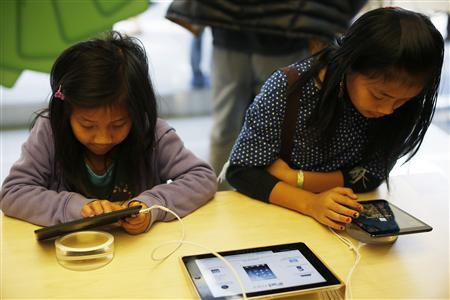 Two children use the iPad Mini at the Apple Store during Black Friday in San Francisco, California, November 23, 2012. REUTERS/Stephen Lam
