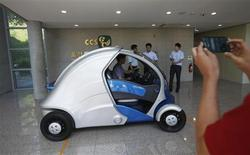 A visitor takes photographs of Armadillo-T, a foldable electric vehicle, at the Korea Advanced Institute of Science and Technology (KAIST) in Daejeon, south of Seoul September 2, 2013. REUTERS/Kim Hong-Ji