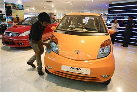 A showroom attendant cleans a Tata Nano car at their flagship showroom in Mumbai May 28, 2013. REUTERS/Vivek Prakash/Files