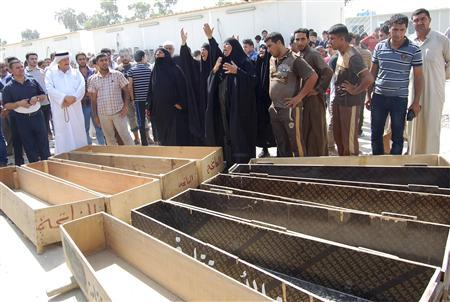 Women react near empty coffins as they wait to claim the bodies of their relatives, who were killed by gunmen, outside a hospital morgue in Mahmudiya, 30 km (19 miles) south of Baghdad, September 4, 2013. REUTERS/Ibrahim Jassam