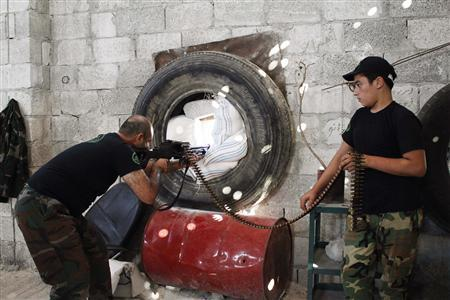 A Free Syrian Army fighter points his weapon as a comrade holds his ammunition in Ramouseh area in Aleppo September 4, 2013. REUTERS/Molhem Barakat