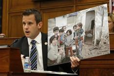 O deputado norte-americano Adam Kinzinger levanta uma foto do que diz serem crianças sírias enquanto fala com o secretário do Estado, John Kerry, no Comitê de Relações Internacionais da Câmara dos EUA em Washington. A Comissão de Relações Exteriores do Senado dos Estados Unidos aprovou uma resolução nesta quarta-feira autorizando uma intervenção militar limitada na Síria, preparando o terreno para um debate no plenário do Senado na próxima semana sobre o uso da força militar. 4/09/2013 REUTERS/Jason Reed