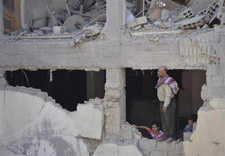 A man and boys inspect a site hit by what activists said was shelling by forces loyal to Syria's President Bashar al-Assad, in the Duma neighbourhood of Damascus September 4, 2013. REUTERS/Bassam Khabieh